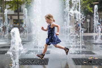 Girl running over fountain