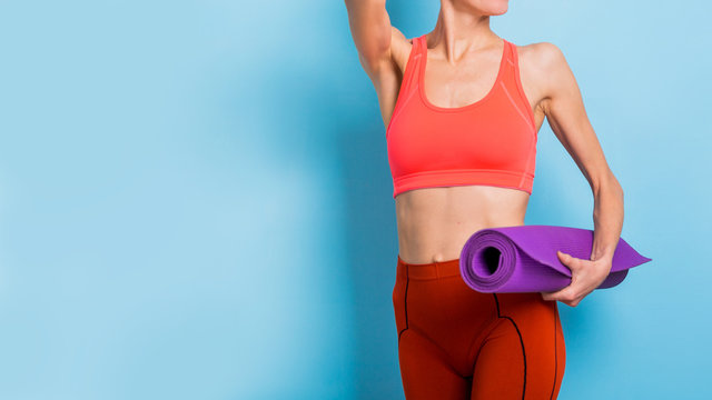 Portrait of happy fitness girl holding yoga exercising mat over light blue background wearing bright sporty outfit of orange color