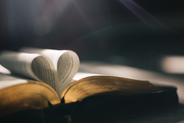 Soft focus open holy Bible at window,heart pages background