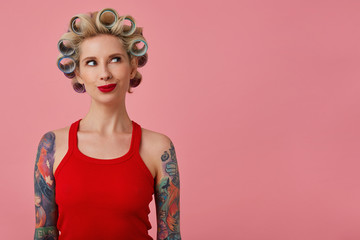 Indoor photo of attractive young blonde female with tattooed hands having curlers on her head and looking excitedly aside, wearing festive makeup while standing over pink background