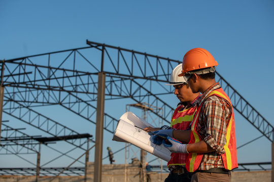 Construction work, Two engineers use blueprint analysis construction at the construction site