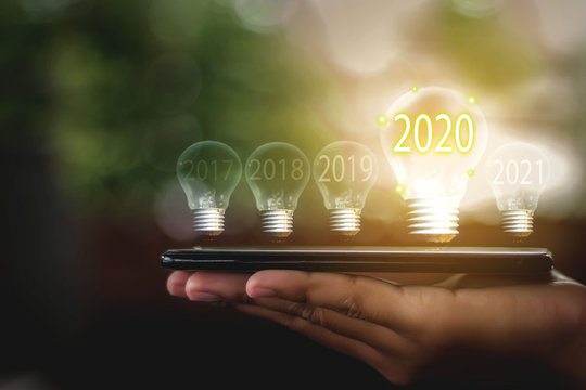 A light bulb that is placed on a smartphone Business man's hand Bright in the year two thousand and twenty, the concept of starting a business in 2020.
