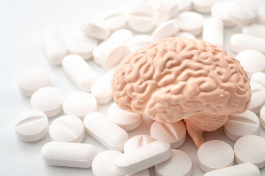 Nootropics use to improve memory and neural function, smart drugs and cognitive enhancers conceptual idea with brain and pills isolated on white background