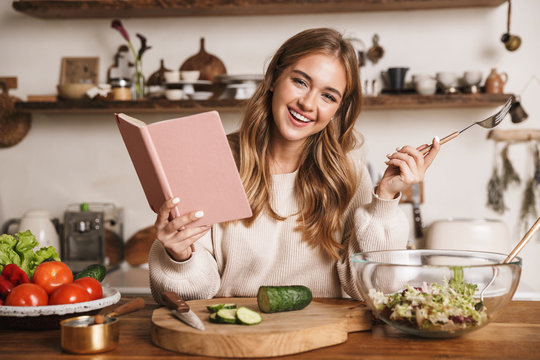 Image of joyful cute woman reading notebook while making dinner