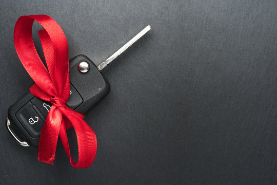 Car key with red bow on dark black slate plate background. Christmas or Valentine's Day gift or present abstract concept. Copy space on the left. Flat lay top view.