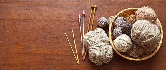 Top view of a wicker basket with balls of wool yarn for hand knitting and a set of hooks and knitting needles on an old wooden table. Place for text, banner. Flat lay, close up, copy space, mock up