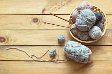 Winter needlework. Balls of wool yarn for hand knitting in a wicker basket and knitting needles on a wooden background. Place for text. Rustic still life. Flat lay, close-up, top view, copy space