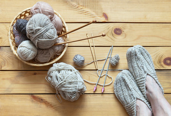 Winter needlework. Female legs in knitted warm slippers and accessories for knitting: balls of woolen yarn, hooks, knitting needles on a wooden background. Flat lay, copy space, close-up, top view