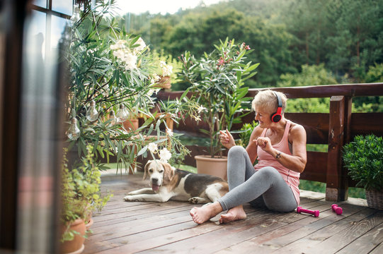 A senior woman with headphones outdoors on a terrace, resting after exercise.