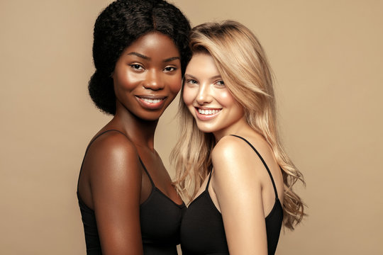 Multi Ethnic Group of Womans with diffrent types of skin  together and looking on camera. Caucasian and African ethnicity womens posing and smiling against beige background.