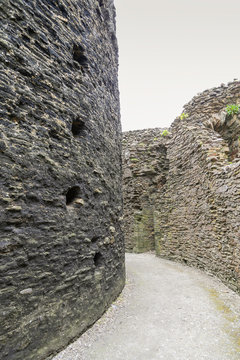 Detail of Inside a motte and bailey Castle in Cornwall.  Crumbling stone walls with a pathway