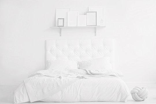 White interior. Bright bed near the white wall.