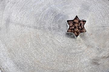 Braune Kaffee Bohnen in einer Form als Stern auf einem Holz Brett Scheibe