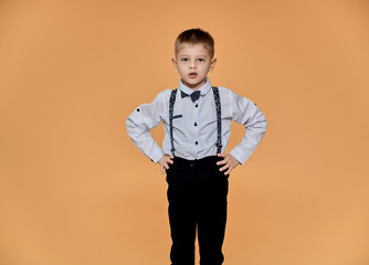 Portrait of a cute boy 10 years old schoolboy on a beige background in trousers and a shirt. Standing right in front of the camera, Shows emotions, talks in different poses.