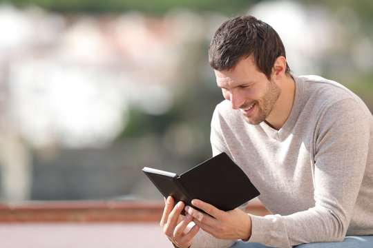 Happy man reading an ebook sitting outdoors