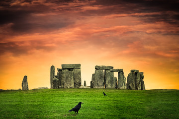Historic Stonehenge under colorful sunset with black crows