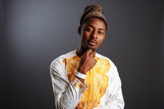 Young man in yoruba and white and gold national clothes standing and posing in gray Background.