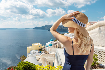 blond woman with a sun hat and a navy blue jumpsuit in Oia on Santorini, the famous blue church domes in the background