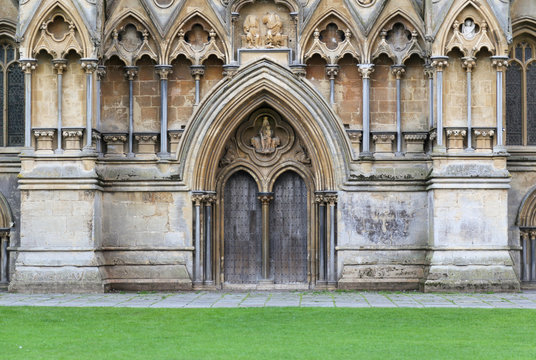 Detail of ornately carved facade and arched door of ancient cathedral in Somerset