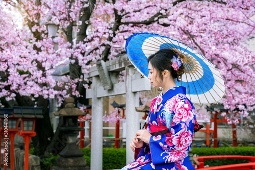 Wall mural Asian woman wearing japanese traditional kimono and cherry blossom in spring, Kyoto temple in Japan.