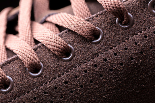 Part of a suede boot with laces. A fragment of brown shoes. A piece of sneaker.