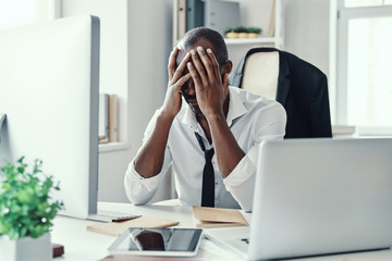 Frustrated young African man in formalwear keeping head in hands head while working in the office