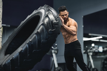 Wall Mural - Shirtless muscular guy flipping huge tire at gym