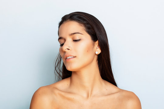 studio portrait of a young Latina with long hair and bare shoulders, close to the camera, with white background, tilting her head to the left, not looking directly in the camera