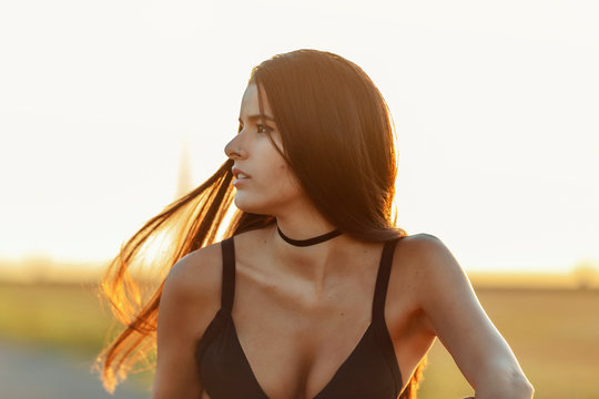 young Latina with long hair, wearing just a bra, hot pants and sneakers, sitting on a lonely road, with the sun setting in the background
