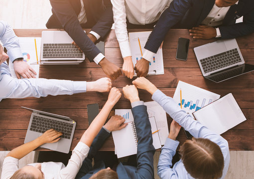 Fist bump of corporate team at meeting in office, top view