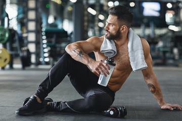 Wall Mural - Pensive bodybuilder with water sitting on floor at gym