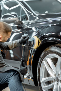 Worker polishing vehicle body with special grinder and wax from scratches at the car service station. Professional car detailing and maintenance concept