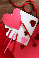 Heart Shaped Valentine's Day Card in Envelope on Table with Art Supplies