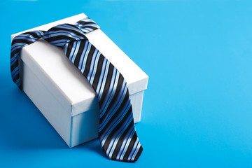 Gift box with blue striped tie. Happy father's day idea, sign, symbol. Holiday background