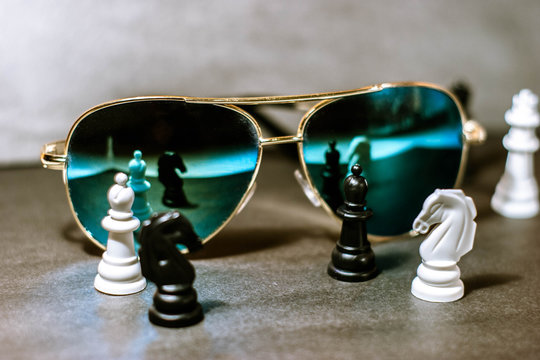 Sunglasses on dark background. Chess. Close up.