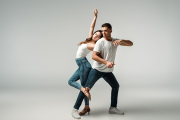 dancers with closed eyes dancing bachata on grey background