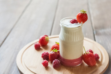 Homemade yogurt in a jar close-up. Fermented milk product with strawberries and copy space.