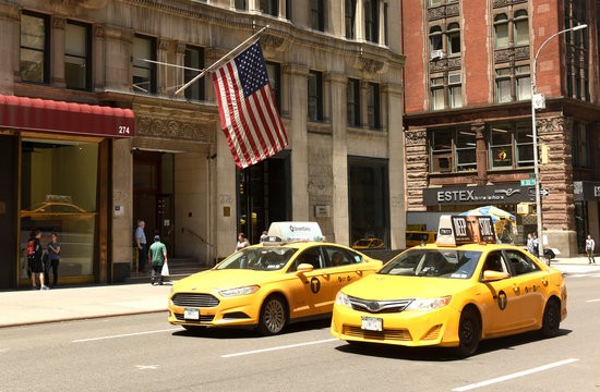 New York, USA - May 30, 2018: Yellow cab and American flag on a building in New York, USA