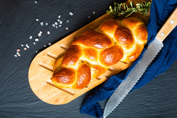 Zelfklevend Fotobehang Brood Homemade food concept fresh baked bread braid challah or brioche on black slate stone with copy space