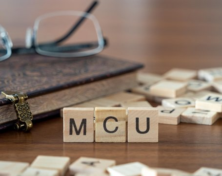 the acronym mcu for Microcontroller concept represented by wooden letter tiles