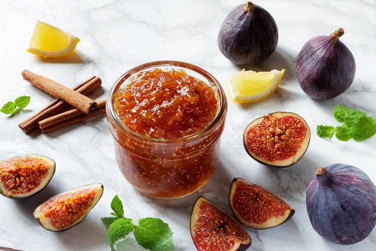 Fresh figs, with a dish of homemade fig jam or preserves with lemon cinnamon sticks and mint on white kitchen marble table background. Healthy breakfast dessert snack recipes and veggie tables concept