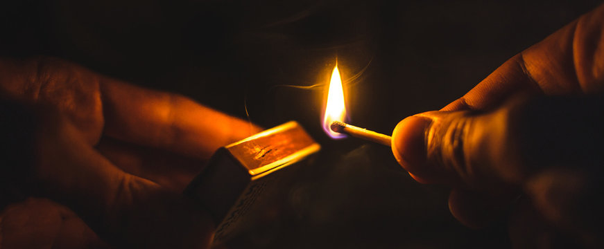 A match lit in the dark in hands with a matchbox