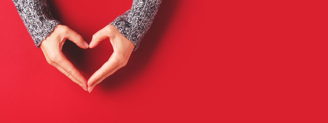 Female hands in shape of heart on red background. Healthcare, love and Valentine's Day concept. Banner for website.