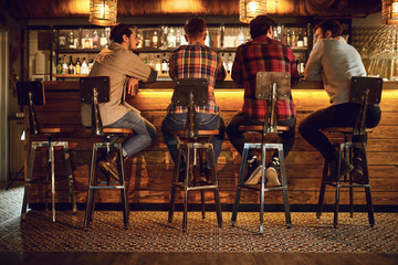 Rear view friends sitting on chairs talking at the bar in a bar.