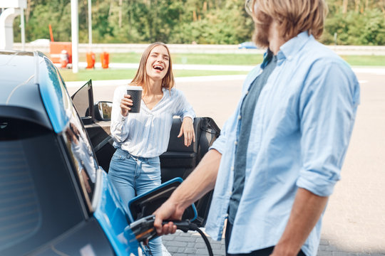 Transportation. Young couple traveling by car having stop at charging station boyfriend plugging in cable looking at girlfriend drinking hot coffee laughing happy