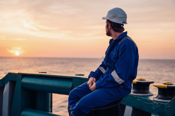 Marine Deck Officer or Chief mate on deck of offshore vessel or ship , wearing PPE personal protective equipment - helmet, coverall. Sunset light Wall mural