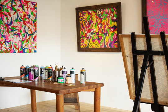 Interior view or art gallery with studio space, easels and cans of spray paint on a table.