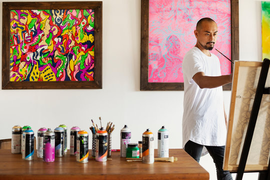 Japanese man standing in art gallery, holding paintbrush, working on artwork on easel.