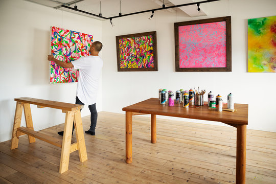Japanese man standing in art gallery, hanging colourful painting on white wall.