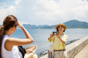 Two Japanese women standing by the ocean, taking picture with mobile phone.